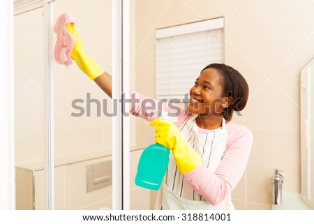 happy african american woman cleaning bathroom