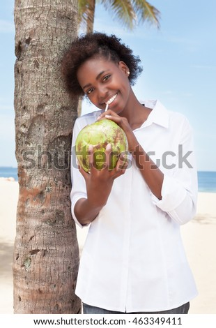 Happy african american woman drinking coconut water