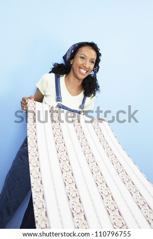 Happy African American woman holding wallpaper - stock photo