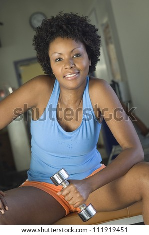 Happy african american woman lifting weights at a gym