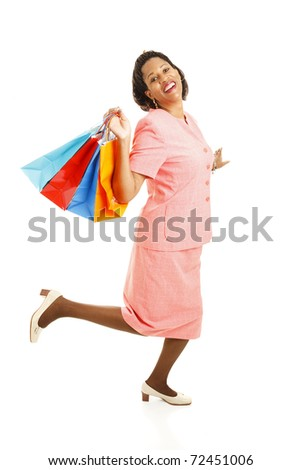 Happy african-american woman skipping along with her shoppping bags.  Full body isolated on white. - stock photo