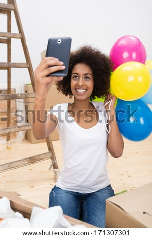 Happy African American woman taking a selfie with her mobile phone as she stands holding a bunch of colourful party balloons to celebrate the move to her new home - stock photo