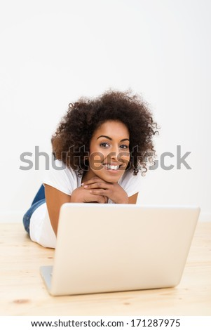 Happy African American woman with a lovely frizzy afro hairdo lying on the wooden floor with a laptop computer smiling at the camera with a blank white wall and copyspace behind her - stock photo