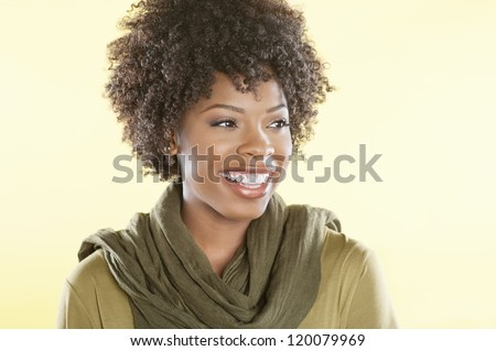 Happy African American woman with a stole round her neck looking away over colored background - stock photo