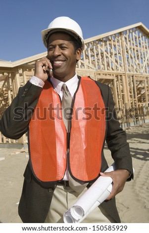 Happy African American worker with blueprints using cell phone at construction site - stock photo