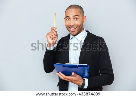 Happy african american young man with clipboard pointing up and having an idea - stock photo