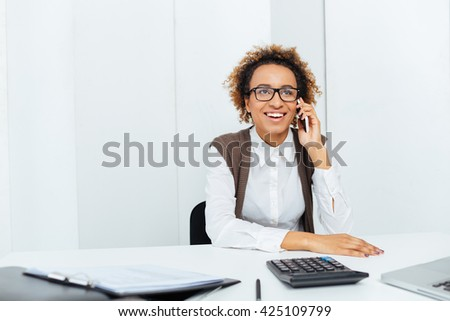 Happy african american young woman accountant sitting and talking on cell phone in office - stock photo