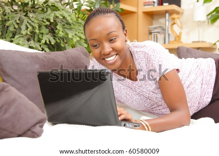 Happy African American young woman using a laptop at home - stock photo