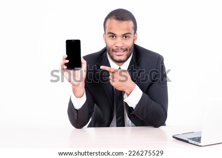 Happy african businessman sitting at the table and pointing at a mobile phone while businessman sitting at the table and working on a laptop isolated on a gray background - stock photo