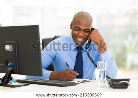 happy african businessman talking on landline phone and writing report - stock photo