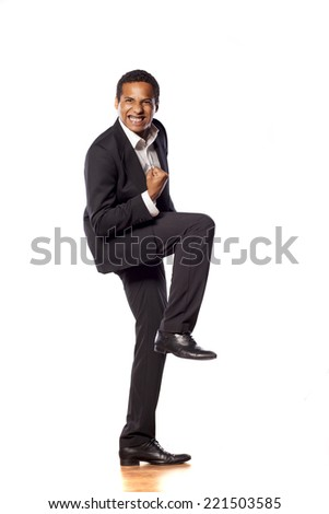 Happy african businessman with winning gesture - stock photo