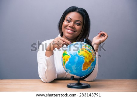 Happy african businesswoman sitting at the table with globe over gray background and looking at camera - stock photo