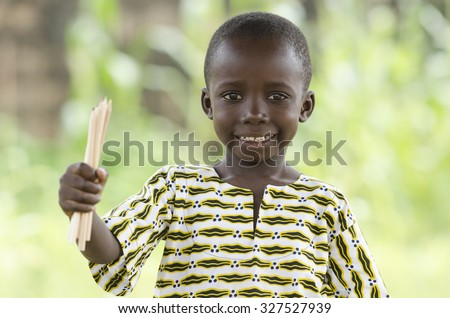 Happy African Child Holding Color Pencils Up Education Symbol. Young handsome African boy holding up color pencils outdoors. Back to school symbol: elementary age student smiling at the camera. - stock photo