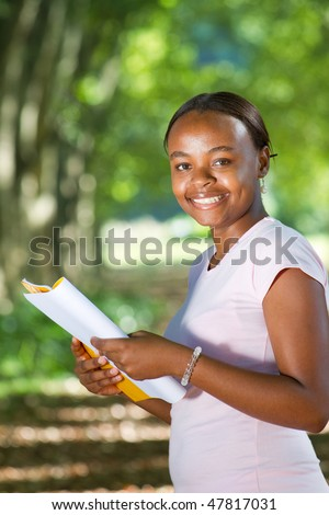 happy african college student reading book in forest - stock photo