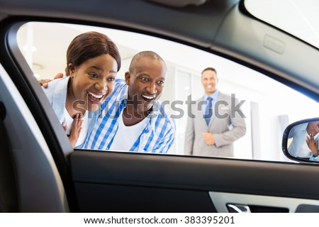 happy african couple choosing luxury car at vehicle dealership looking at the interior - stock photo