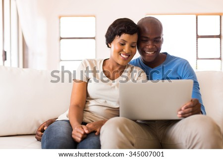 happy african couple looking at laptop screen at home