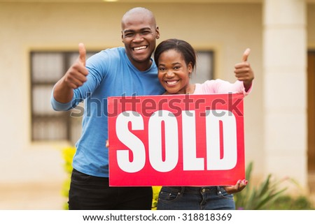 happy african couple outside home with sold sign giving thumbs up - stock photo