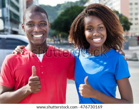 Happy african couple showing thumbs up