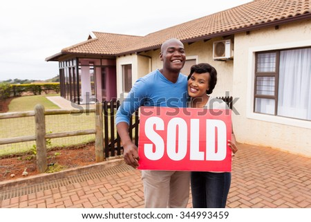 happy african couple standing outside their house and holding sold sign - stock photo