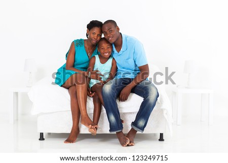 happy african family sitting on bed - stock photo