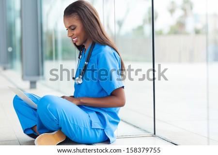 happy african female nurse using laptop sitting at hospital floor - stock photo
