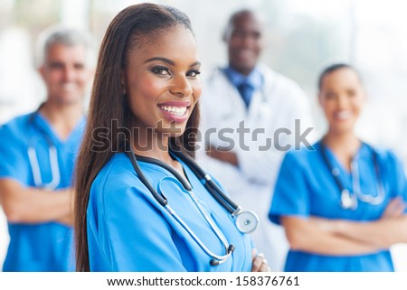 happy african female nurse with colleagues on background - stock photo