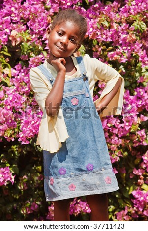 happy African  girl against red flowers background - stock photo