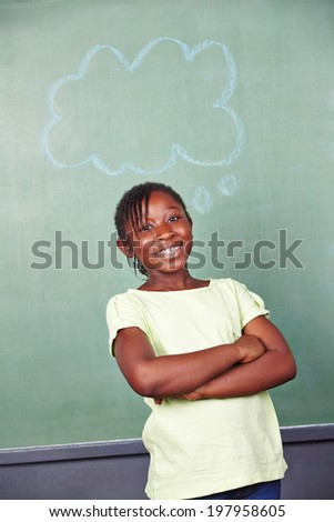 Happy african girl with thought bubble at chalkboard in elementary school - stock photo