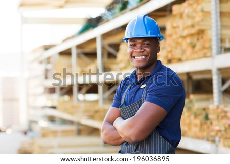 happy african industrial worker standing at building material warehouse - stock photo