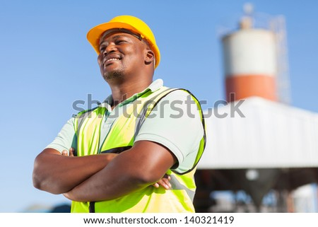 happy african male constructor with arms folded - stock photo
