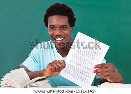 Happy African Male Student Showing A Paper With Perfect Grade A Plus In Classroom - stock photo