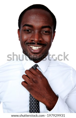 Happy african man adjusting his necktie over white background