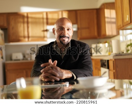 happy african man at home at kitchen table portrait - stock photo