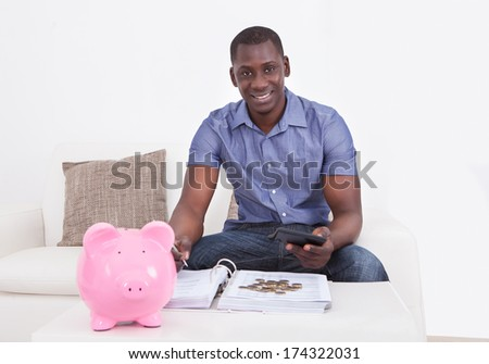 Happy African Man Sitting On Couch With Document And Piggybank - stock photo