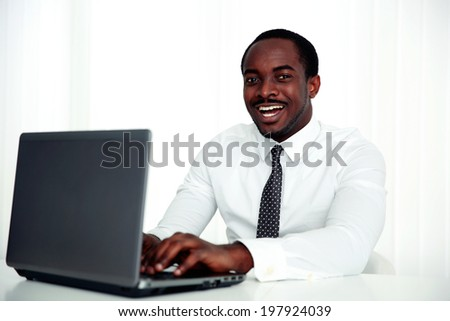 Happy african man using laptop in office
