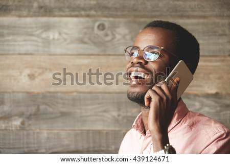 Happy African man wearing glasses, talking on mobile phone with his family while being away on business trip, posing against wooden copy space wall for your information. Technology and connection - stock photo