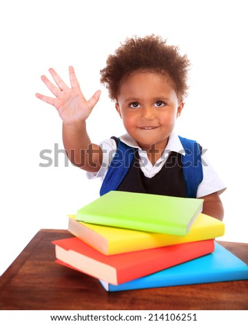 Happy African preschooler sitting behind desk with many books on it, isolated on white background, raised up hand and say hello, back to school concept - stock photo