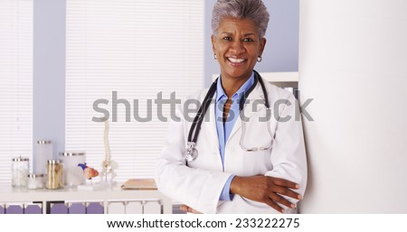 Happy African Senior doctor standing in office  - stock photo