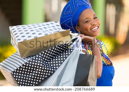 happy african shopper carrying shopping bags in mall - stock photo