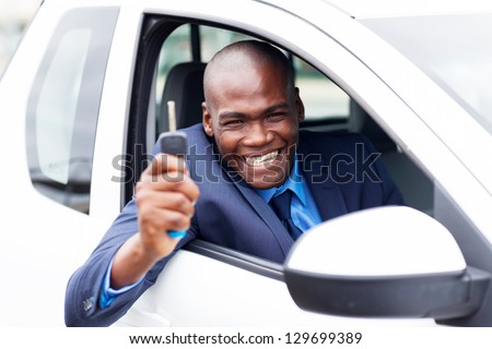 happy african vehicle buyer inside his new car with car key - stock photo