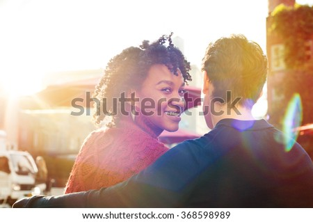 Happy african woman and young man sit on bench while looks at camera in a cafe. Close up of loving couple sitting in a cafeteria. Young smiling woman with friend looking at camera.  - stock photo