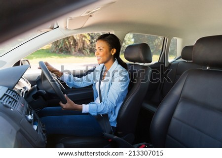 happy african woman driving a new car - stock photo
