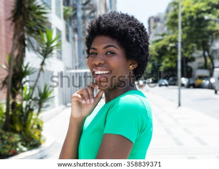Happy african woman in a green shirt in the city - stock photo