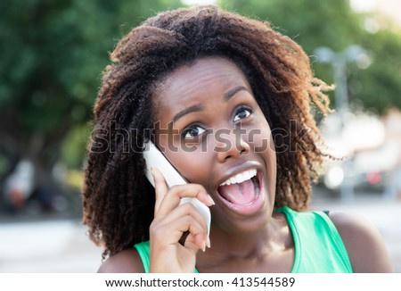 Happy african woman in a green shirt outdoor at phone - stock photo