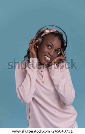 Happy African Woman listening to music on headphones. Young fresh African female model on blue background. - stock photo