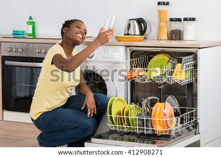 Happy African Woman Looking At Clean Glass Crouching Near Dish Washer