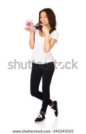 Happy african woman pointing on piggybank. - stock photo