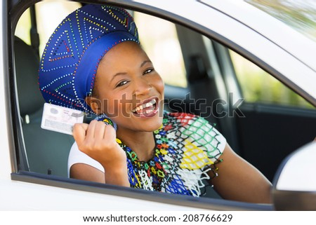 happy african woman showing her driver's license she just got - stock photo