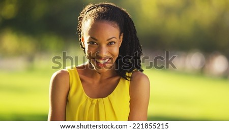 Happy African woman smiling in a park - stock photo