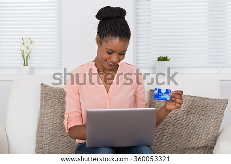 Happy African Woman Using Debit Card For Shopping Online On Laptop - stock photo